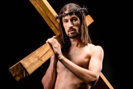 Photo pour Homme torse nu en couronne avec des pointes tenant croix isolé sur noir - image libre de droit