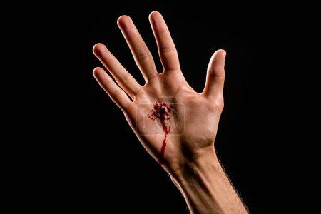 Photo pour Vue recadrée de l'homme religieux avec la main sanglante isolé sur noir - image libre de droit