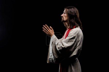 Photo pour Vue latérale de l'homme avec les mains priantes isolé sur noir - image libre de droit