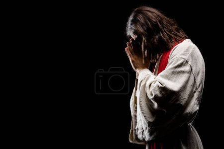 Photo for Religious man covering face while praying isolated on black - Royalty Free Image