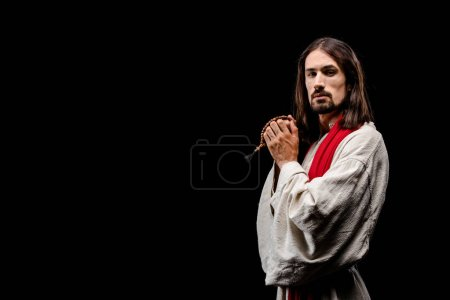 Photo for Handsome man looking at camera and holding rosary beads isolated on black - Royalty Free Image