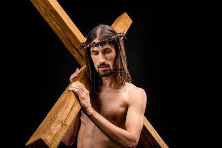 Photo for Sad shirtless man in wreath holding cross isolated on black - Royalty Free Image