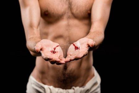 Photo pour Vue recadrée de l'homme avec les mains sanglantes d'isolement sur le noir - image libre de droit
