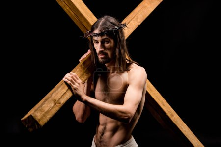 Photo for Upset shirtless man in wreath holding cross isolated on black - Royalty Free Image