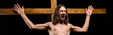Photo for Panoramic shot of shirtless man crucified on wooden cross screaming isolated on black - Royalty Free Image