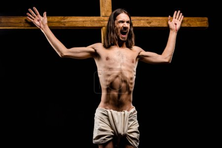 Photo for Shirtless man crucified on wooden cross screaming isolated on black - Royalty Free Image