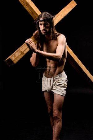 Photo for Bearded shirtless man in wreath holding wooden cross isolated on black - Royalty Free Image