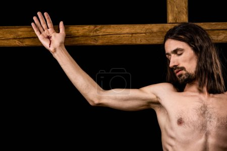 Photo for Jesus crucified on wooden cross isolated on black - Royalty Free Image