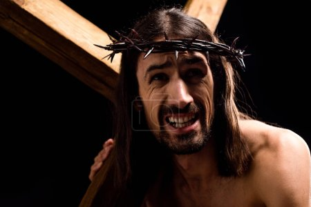 Photo for Jesus holding heavy wooden cross isolated on black - Royalty Free Image