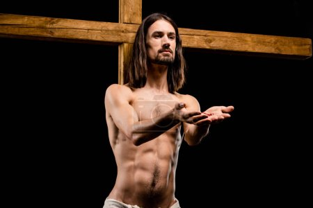 Photo for Jesus with cupped hands near wooden cross isolated on black - Royalty Free Image