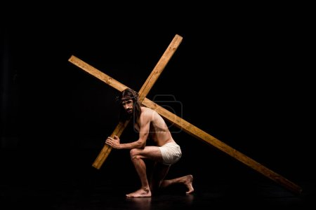 Photo for Shirtless jesus sitting and holding wooden cross on black - Royalty Free Image