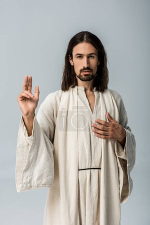 Photo for Handsome man in jesus robe with hand on chest gesturing isolated on grey - Royalty Free Image