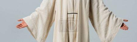 Photo pour Coup panoramique de l'homme en robe de Jésus avec les mains tendues isolées sur gris - image libre de droit