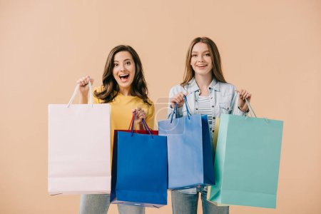 Photo for Attractive and smiling friends holding shopping bags isolated on beige - Royalty Free Image
