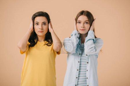 Photo pour Amis attrayants touchant leurs oreilles et regardant l'appareil-photo isolé sur le beige - image libre de droit