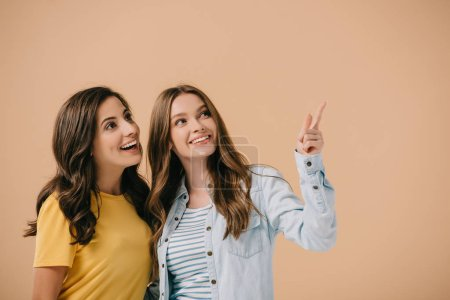 Photo for Attractive and smiling friends pointing with finger isolated on beige - Royalty Free Image