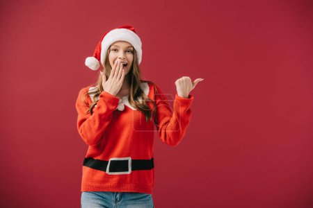 Photo for Attractive woman in santa hat and sweater pointing with finger isolated on red - Royalty Free Image