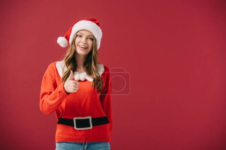 Photo for Attractive woman in santa hat and sweater showing thumb up isolated on red - Royalty Free Image