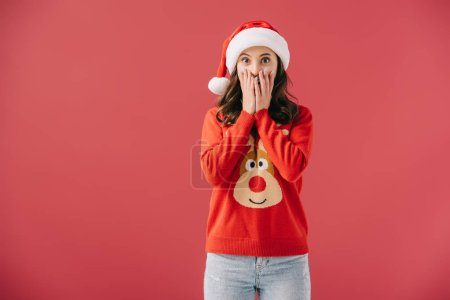 Photo for Attractive and shocked woman in santa hat and sweater looking at camera isolated on red - Royalty Free Image