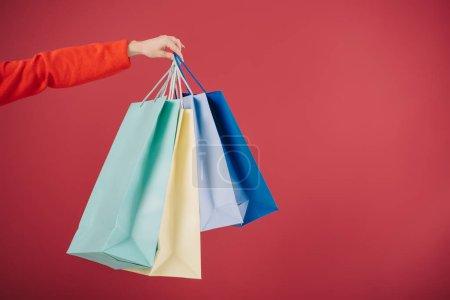 Photo pour Vue recadrée de femme tenant des sacs à provisions isolés sur rouge - image libre de droit