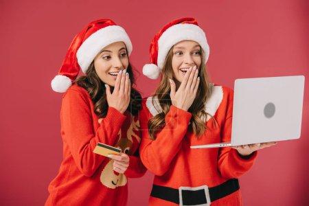 Photo pour Femmes attirantes et souriantes dans des chandails et l'ordinateur portatif de fixation de santa et la carte de crédit d'isolement sur le rouge - image libre de droit