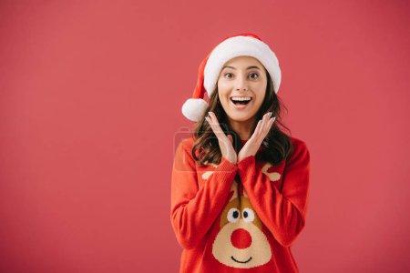 Photo pour Attrayant et souriant femmes en chandails et chapeaux santa regardant caméra isolée sur rouge - image libre de droit