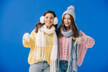 attractive and smiling women in sweaters and scarves pointing with fingers and looking at camera isolated on blue
