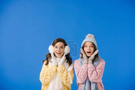 Photo for Attractive and shocked women in sweaters and scarves looking at camera isolated on blue - Royalty Free Image