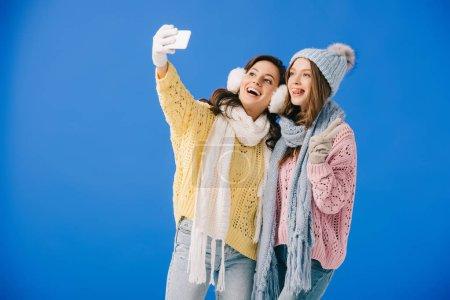 Photo pour Femmes attirantes et souriantes dans des chandails et des écharpes prenant le selfie et affichant le signe de victoire d'isolement sur le bleu - image libre de droit