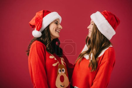 Photo for Attractive and smiling women in sweaters and santa hats looking at each other isolated on red - Royalty Free Image