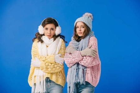 Photo pour Femmes attirantes dans des chandails et des écharpes se sentant froid et regardant l'appareil-photo isolé sur le bleu - image libre de droit