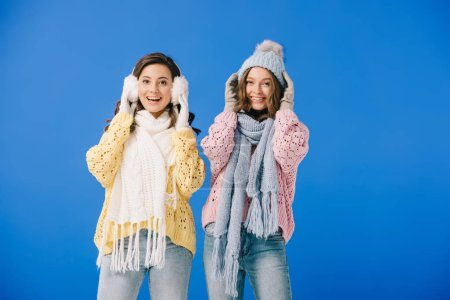 Photo for Attractive and smiling women in sweaters and scarves looking at camera isolated on blue - Royalty Free Image