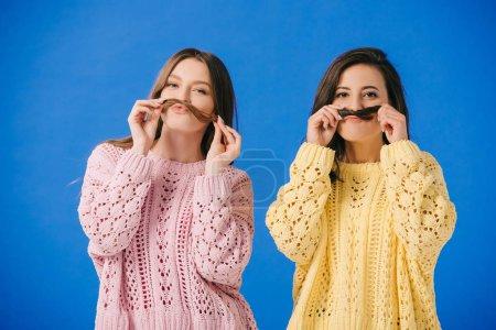 Photo pour Femmes attirantes dans des chandails jouant avec le cheveu regardant l'appareil-photo isolé sur le bleu - image libre de droit
