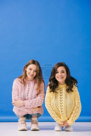 Photo for Attractive and smiling women in sweaters looking at camera on blue background - Royalty Free Image