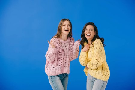 Photo for Attractive and smiling women in sweaters looking at camera isolated on blue - Royalty Free Image