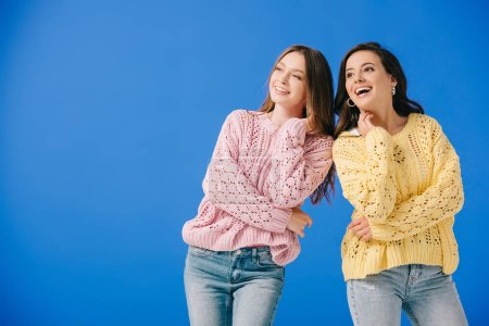 Photo for Attractive and smiling women in sweaters looking away isolated on blue - Royalty Free Image