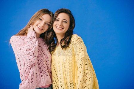 Photo pour Femmes attirantes et souriantes dans des chandails regardant l'appareil-photo isolé sur le bleu - image libre de droit