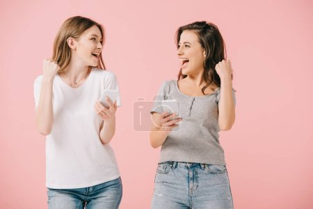 Photo for Attractive and smiling women in t-shirts holding smartphones and showing yes gesture isolated on pink - Royalty Free Image