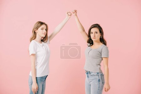 Photo for Attractive women in t-shirts showing fists and looking at camera isolated on pink - Royalty Free Image