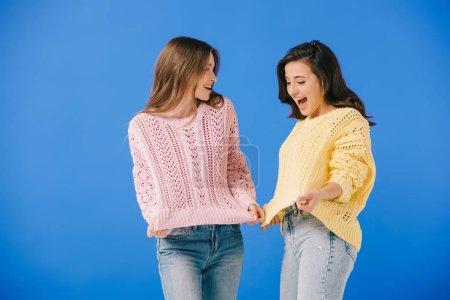 Foto de Mujeres atractivas y sonrientes en suéteres mirándose unas a otras aisladas en azul - Imagen libre de derechos