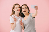 attractive and smiling women in t-shirts taking selfie and showing peace signs isolated on pink