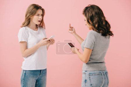 woman in t-shirt holding smartphone and showing middle finger to her friend isolated on pink
