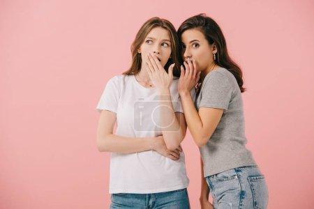 Foto de Mujer atractiva diciendo secreto a su amigo sorprendido en camiseta aislada en rosa - Imagen libre de derechos