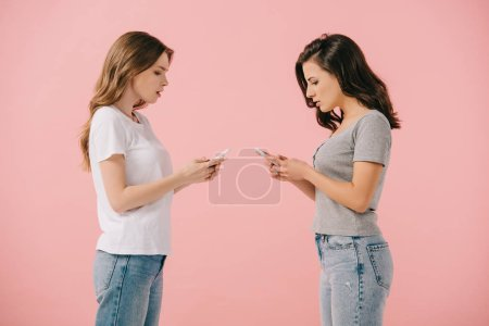 Photo for Side view of attractive and shocked women in t-shirts using smartphones isolated on pink - Royalty Free Image