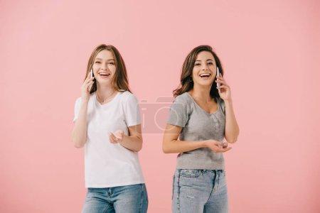 Photo pour Femmes attirantes et souriantes dans des t-shirts parlant sur des smartphones isolés sur le rose - image libre de droit