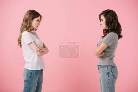 Photo pour Séduisantes et sérieuses femmes en t-shirts aux bras croisés se regardant isolées sur rose - image libre de droit