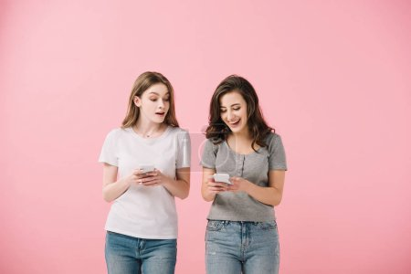 Photo pour Femmes attirantes et souriantes dans des t-shirts retenant le smartphone d'isolement sur le rose - image libre de droit
