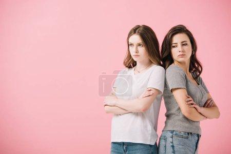 Photo pour Femmes attirantes et tristes dans des t-shirts avec les bras croisés regardant loin isolé sur le rose - image libre de droit