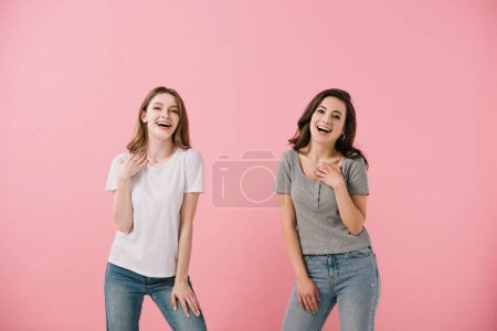 Photo pour Femmes attirantes et souriantes dans des t-shirts regardant l'appareil-photo isolé sur le rose - image libre de droit