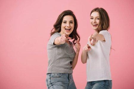 Photo pour Femmes attirantes et souriantes dans des t-shirts pointant avec des doigts isolés sur le rose - image libre de droit